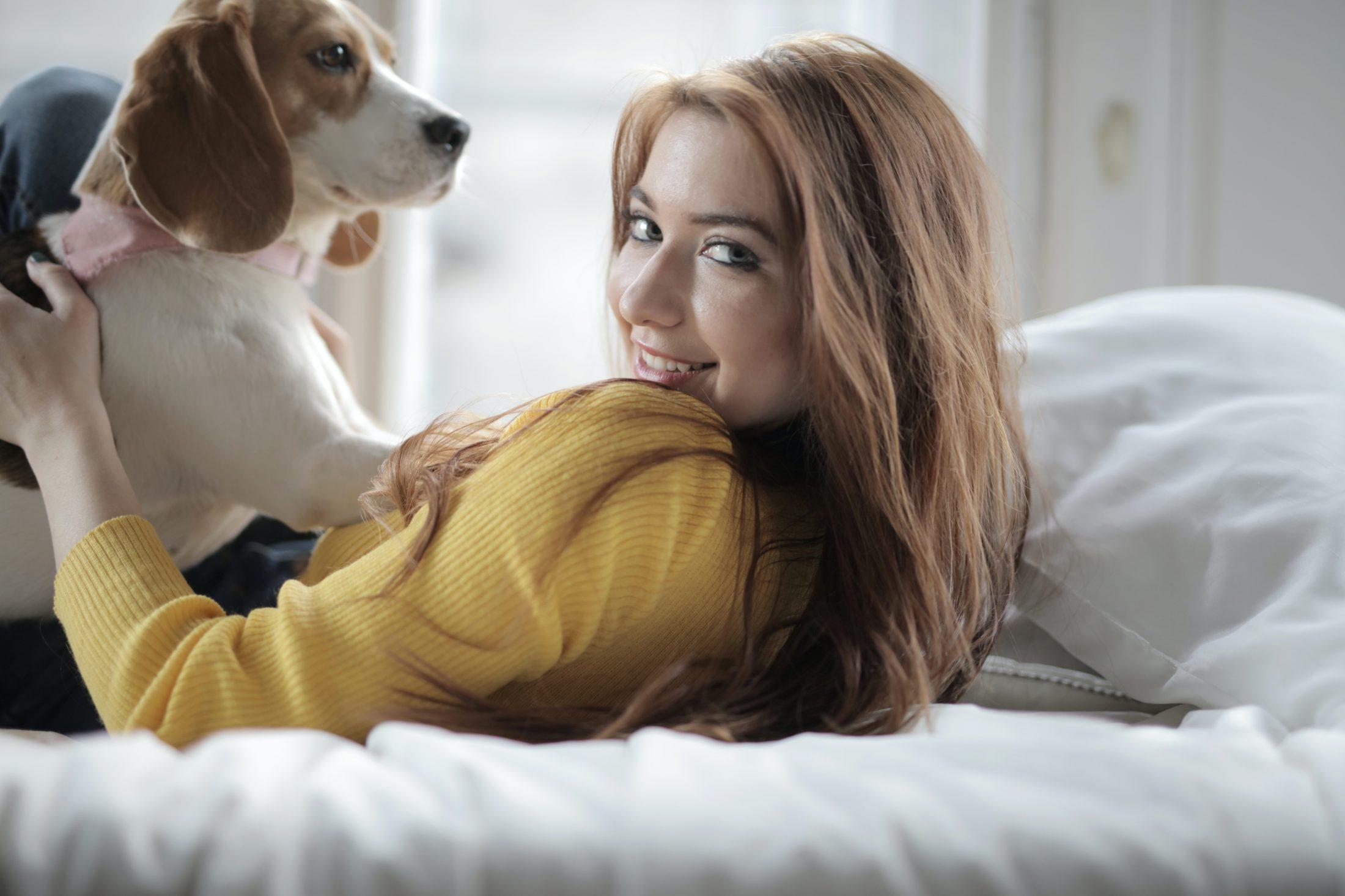 dona com seu cachorro no colo deitada na cama