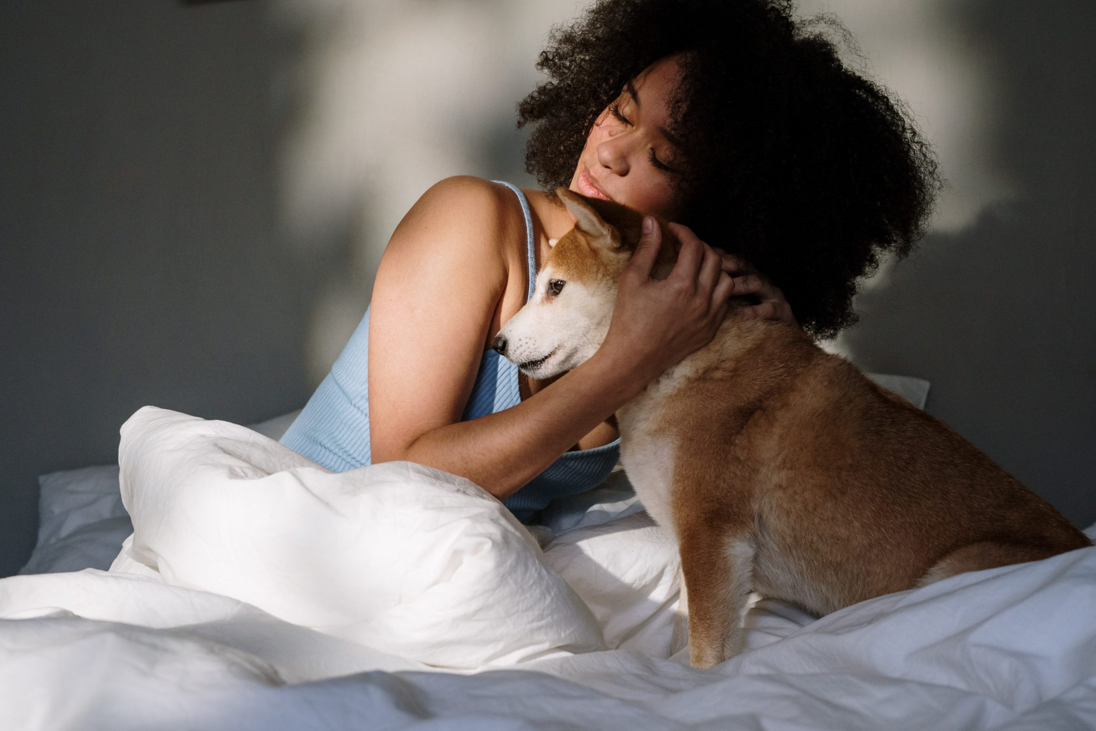 mulher abraçando cachorro na cama
