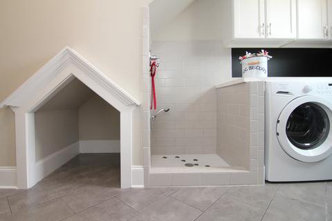 Casinha de cachorro incorporada à lavanderia.