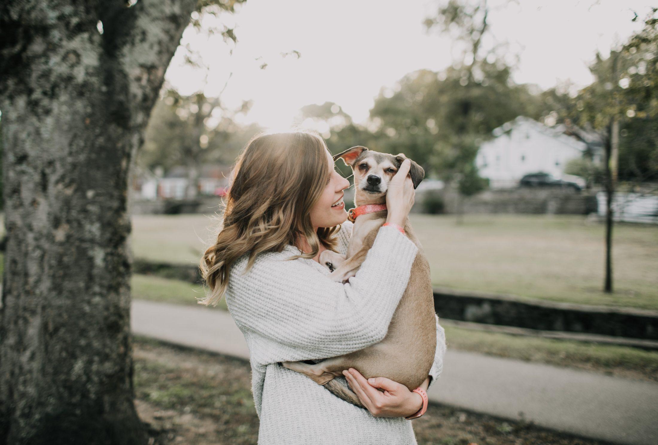 mulher com cachorro no colo retribuindo a devoção canina