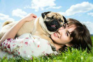 Vínculo com cachorro: Dona abraçada ao seu Pug deitada na grama do jardim.