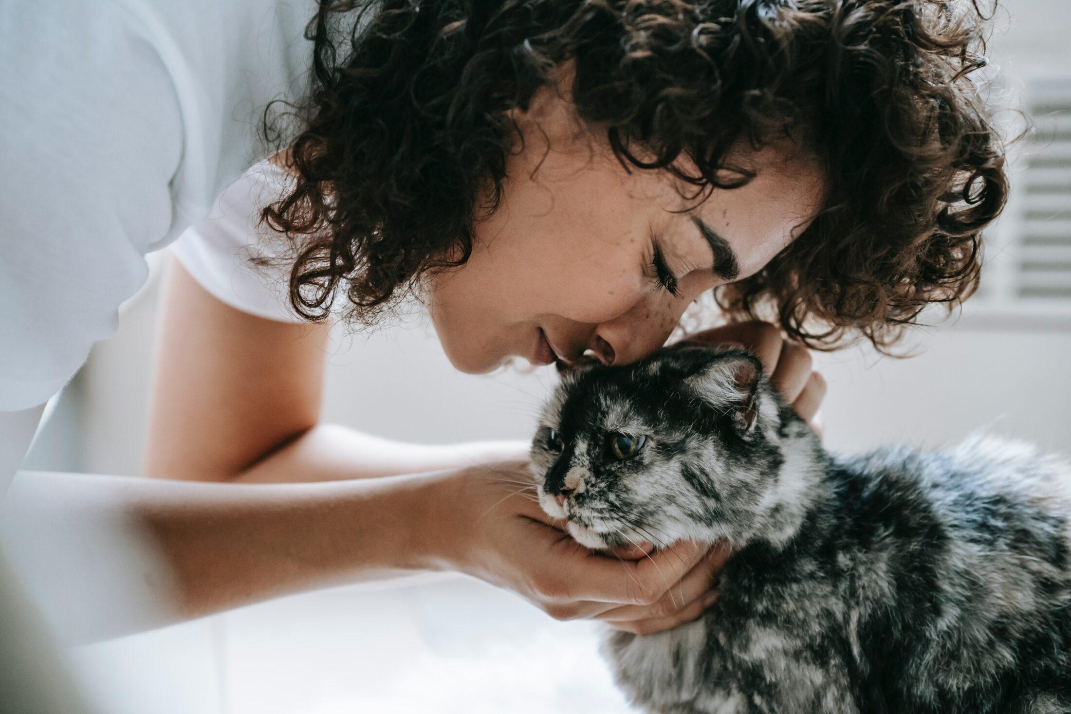 mulher com rosto colado no gato fazendo carinho