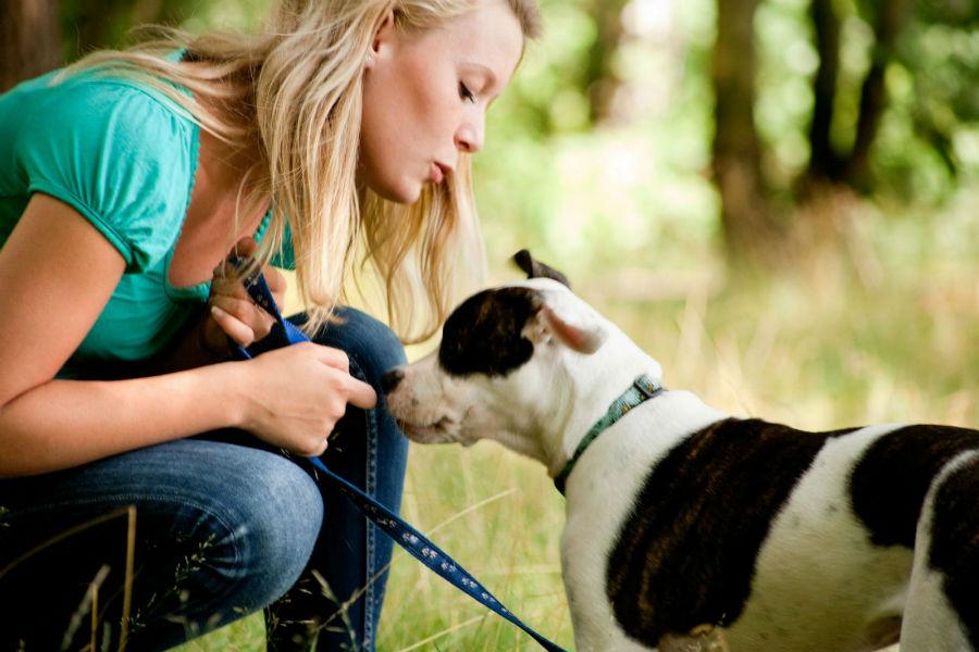 Atividades físicas para cães: Dona e seu cachorro conversando após uma caminhada.